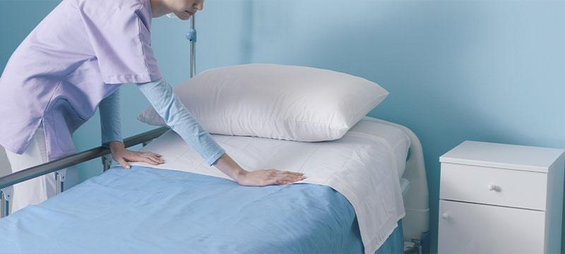 Wäscherei Pauli, das sind Wäscheprofis für Kliniken. Hier: Eine Klinikmitarbeiterin, die ein bett vorbereitet.
