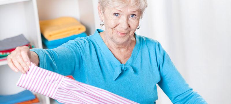 Wäscherei Pauli, das sind Wäscheprofis für Seniorenheime. Hier: Eine ältere Dame legt Wäsche zusammen.