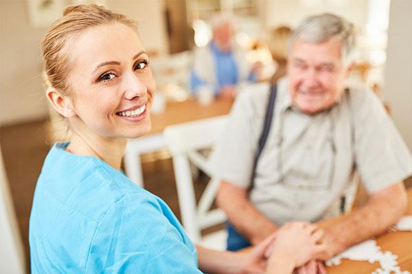 Senioren- & Pflegeheime - Berufsbekleidung. Hier im Bild: Eine Pflegekraft bei der Bewohnerbetreuung.