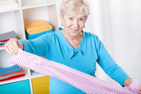 Senioren- & Pflegeheime - Bewohnerwäsche. Hier im Bild: eine nette Helferin, die Wäsche zusammenlegt.
