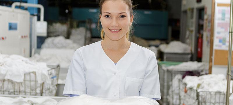 Wäscherei Pauli, das sind Wäscheprofis mit Qualität. Hier: Junge Frau im Wäschereibetrieb.